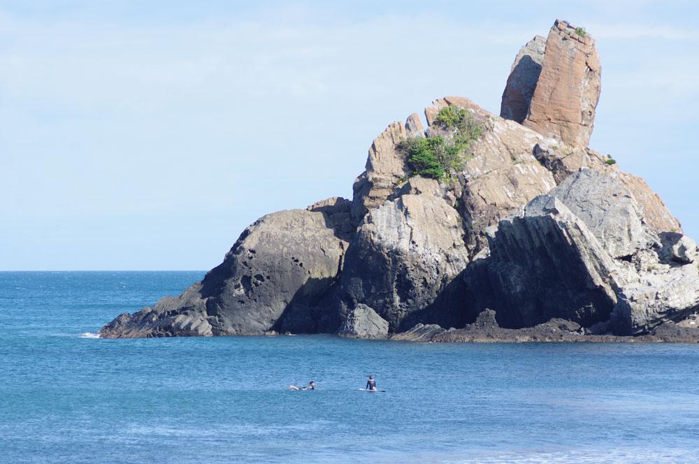 立神岩はサーフィンの聖地としても知られる